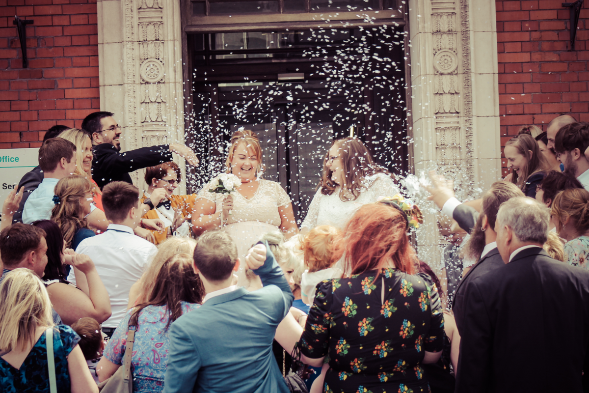 bride and bride smiling with confetti